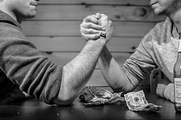 two men armwrestling on table black and white